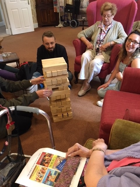 Residents play giant Jenga with the volunteers