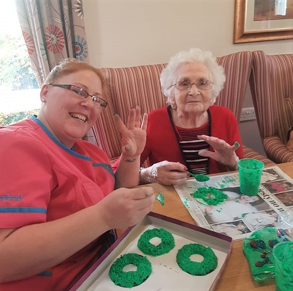 Ashbourne Court Care Home, Hampshire-Magic Moments Club Assistant Nemily and resident Edith having fun painting Christmas wreaths