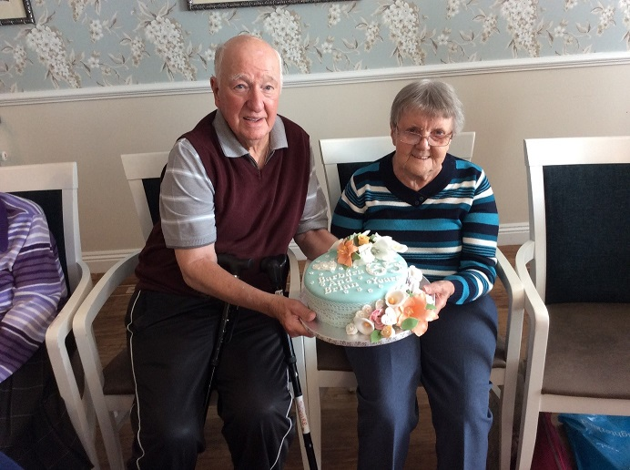 Barbara and Brian holding their cake