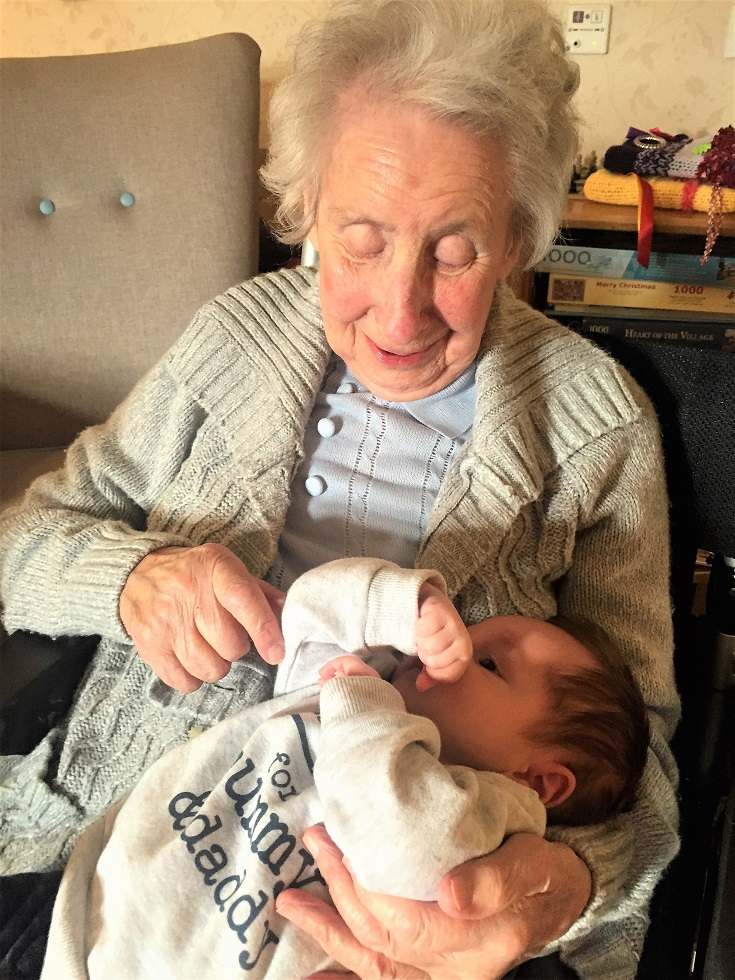 Resident Barbara cuddling her new great-grandson Theo