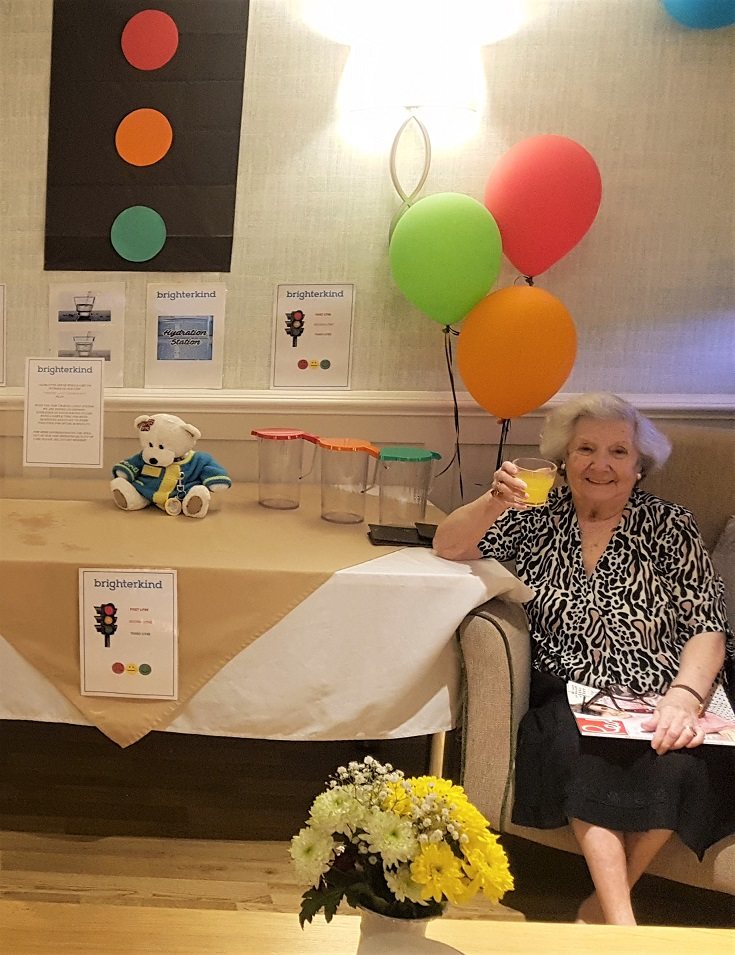 Charlotte House Care Home, The Wirral-Resident Juanita raises a glass to our new traffic light hydration system