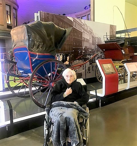 Resident Betty in front of some of the old fashioned carriages