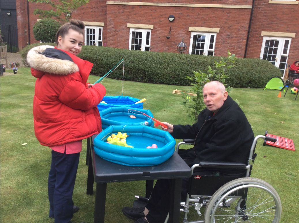 Elm Bank Care Home, Kettering-Magic Moments Club Assistant Chloe and resident Alan go head to head in the hook a duck competition