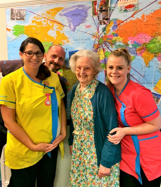 Hamilton House Care Home, Buckingham-Senior Carer Lisa, Maintenance Man John, resident Betty and Magic Moments Club Coordinator Rosie in front of our map of the world showing where our postcards have come from