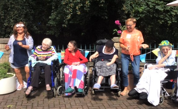 Henleigh Hall Care Home-Team member Jeanette, residents Joan, Jean and Sue, Home Manager Lindsey and resident Nora enjoying the live music