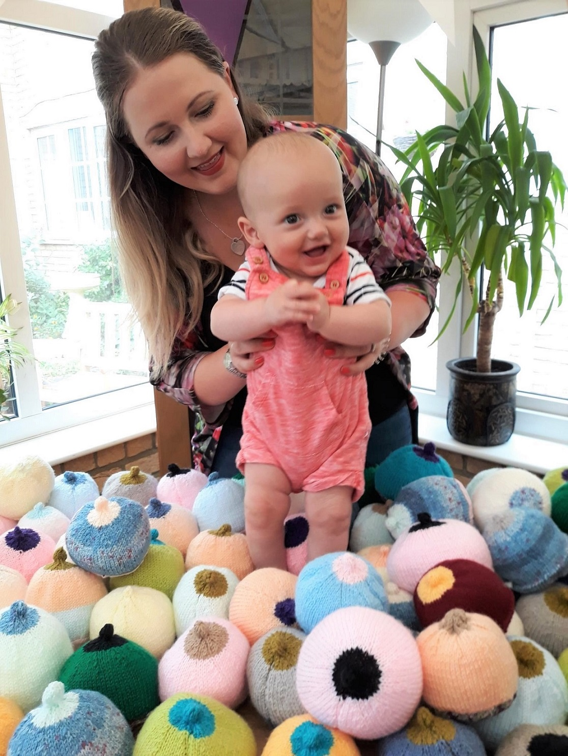 Highfield Care Home, Hertfordshire-That's one happy baby! Mum Briony with her son Henry who looked delighted to be among our knitted boobies