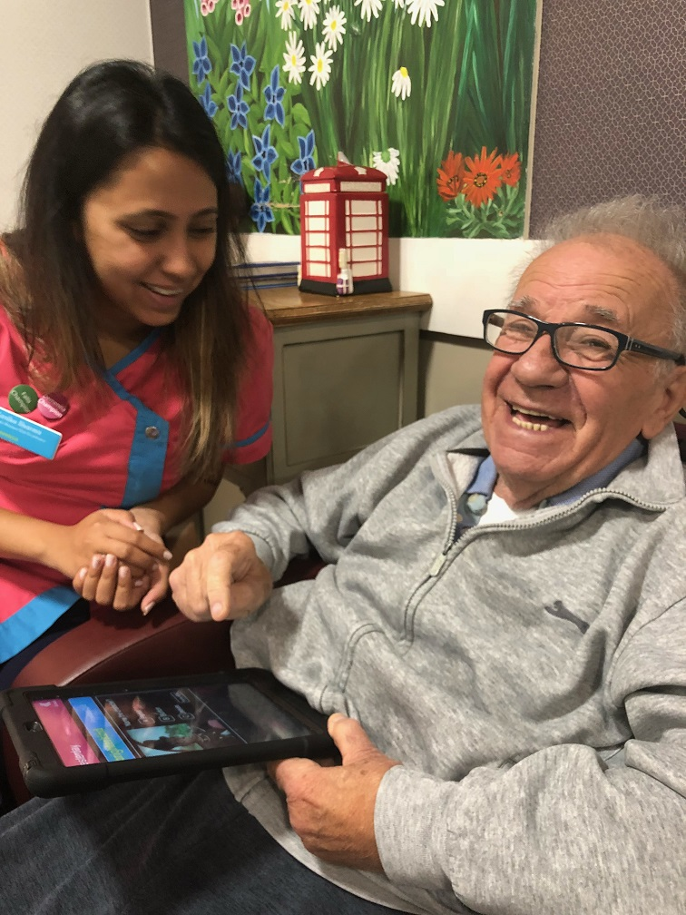 Resident Royston with team member Kanika enjoying the quizzes on the new Magic Moments Club App