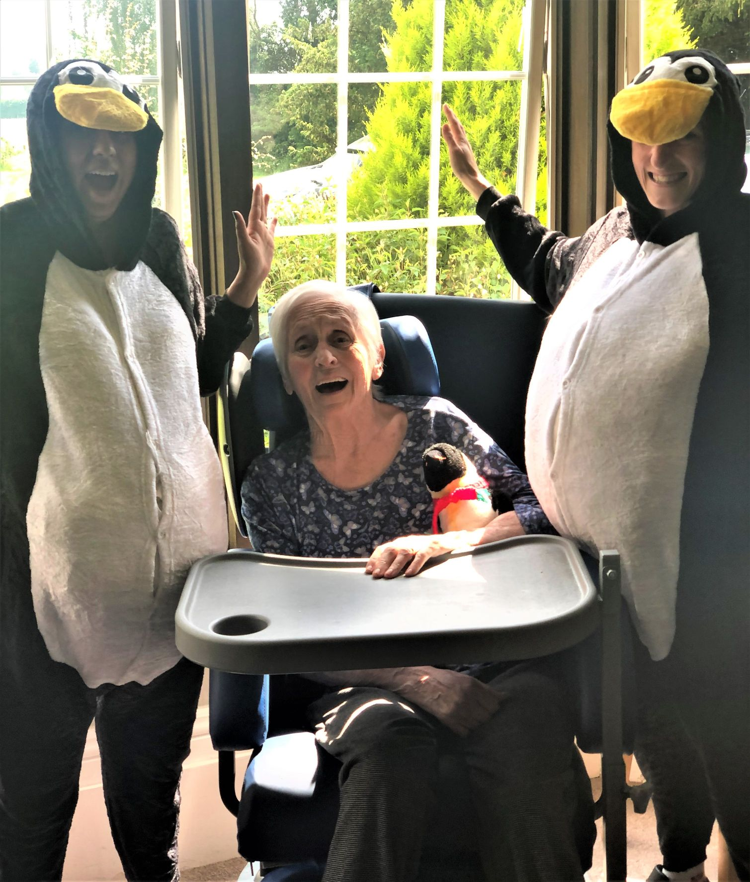 Hungerford Care Home, Berkshire-Resident Sylvia was delighted to meet Percy and Pingu, aka Magic Moments Club Coordinators Kanika and Sarah