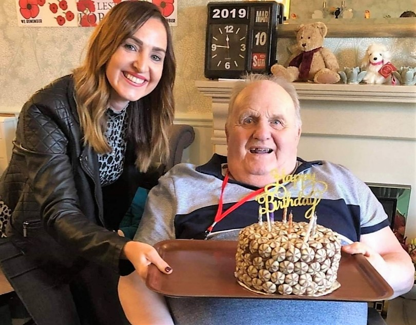 Ivybank House Care Home, Bath -'Bake a Smile Project' volunteer Shona presents resident Mike with his wonderful birthday cake