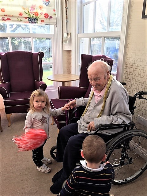 Mya holds hands with resident Glynn while little Arthur checks out his wheelchair