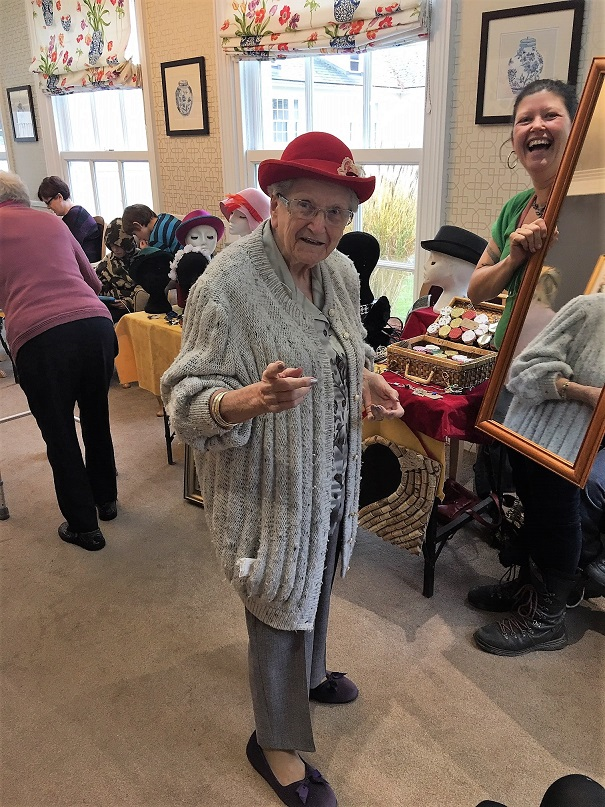 Resident Pam trying on one of the hats from the millinery stall