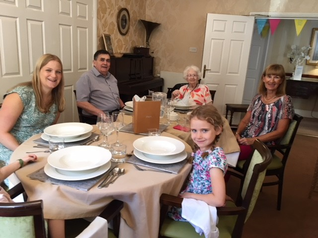Resident Jean Clayton with her family seated for their special lunch
