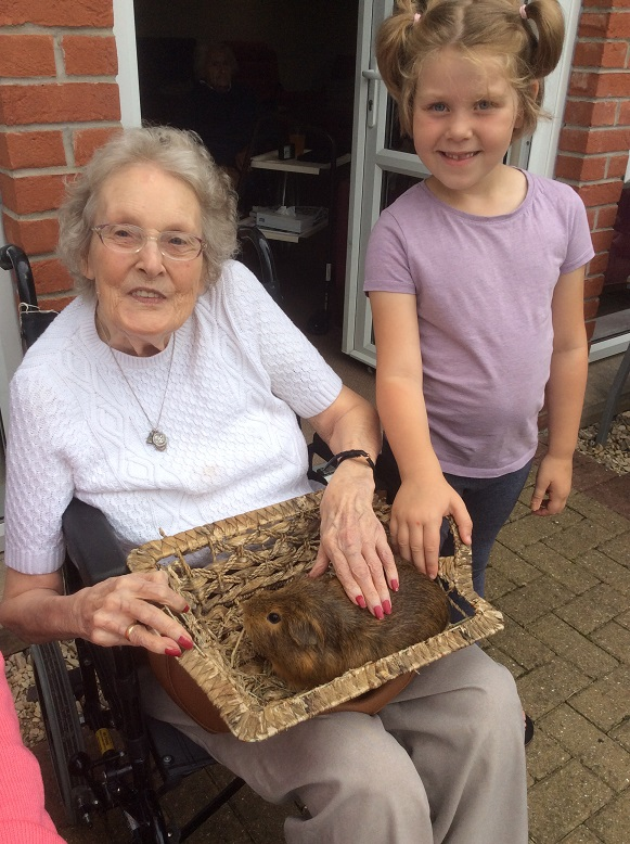 Resident Shirley Vincent & visitor Amelia stoking a guinea pig
