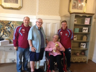 Coach Paul Bunting, residents Ivan Welch and Brenda Scott and Manager Dan Bunting with the League Trophy