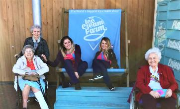A breath of fresh air and more for Rita's wish at Charlotte House Care Home - The team enjopy their glorious day and pose around a giant deck chair!