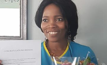 Brenda holding her certificate and presents