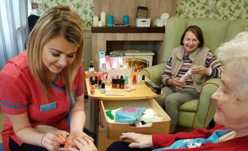 Activity coordinator, Natalie Fitch, painting June Thomas' nails
