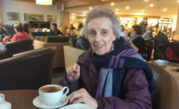 Wendy about to enjoy her coffee and cake in the garden centre cafe
