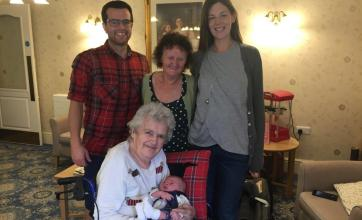 Margaret cuddles her Great Grandson Jenson, surrounded by her family