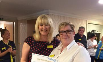 Kelly receiving her award from regional manager, Bev Jewitt, with members of the team supporting her