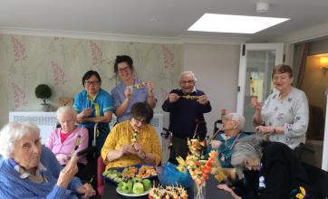 Residents Lucienne, Kathleen, Anne Marie, Eric, Marjorie, Mavis and Lilly with Carers Emy and Tamara and their fantastic fruit creations