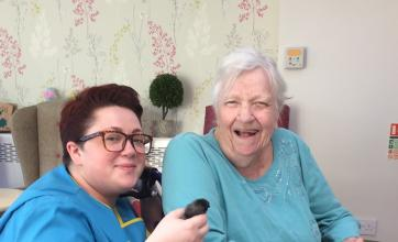 Carer Erin introducing resident Margaret to one of the chicks