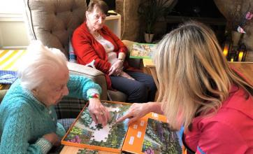 Mill House Care Home, Oxfordshire-Magic Moments Club Coordinator Linda helps resident Sheila with her jigsaw