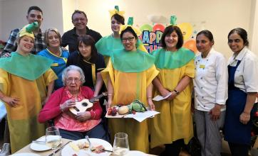 Birthday girl Joan holding the ukulele surrounded by her grandson Michael and team members at Springfield House
