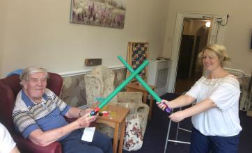 Resident Fred and Activities Assistant Laura have a lightsaber duel