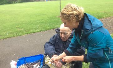 Abby from Greenspace Trust helping resident Jack to start a spark for the fire