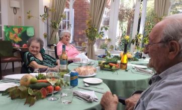 Residents Frantz, Evelyn and Barbara enjoying a pre-lunch drink