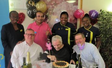 Uplands Care Home, London-Frederick cutting one of his 3 birthday cakes surrounded by his sons and team members at Uplands Care Home