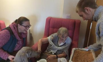 Barbara, her daughter and Mila the dog eyeing up the cake brought in by the students