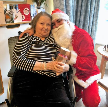 Hungerford Care Home, Berkshire. Resident Annie Emmons enjoys a festive cuddle with Father Christmas (Care Assistant Tiago Casthaneira)