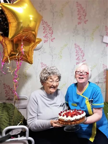 Resident Maisie is presented with her birthday cake by Carer Tricia Connolly