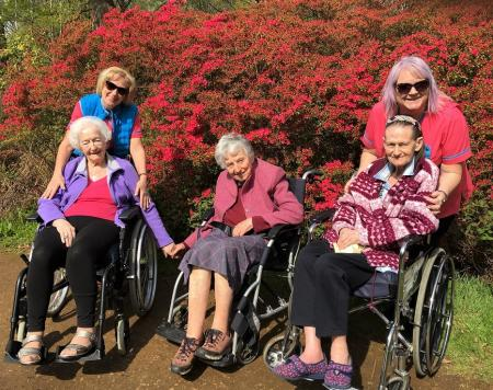 Emberbrook Care Home, Surrey-Residents Audrey, Charmin and Sonya with Magic Moments Club Coordinators Agnes and Claire in front of one of the beautiful Azaleas at the Isabella Plantation
