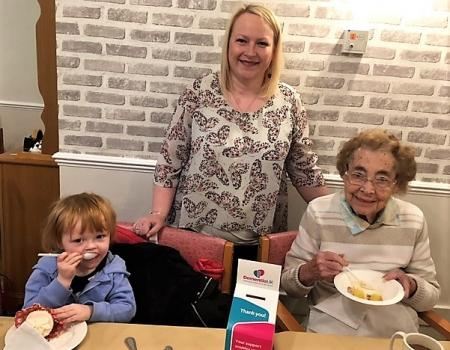 Springfield House Care Home. Nurse Katie, her daughter Isobel and resident Margaret enjoying cakes at our 'Time for a Cuppa' event for Dementia UK
