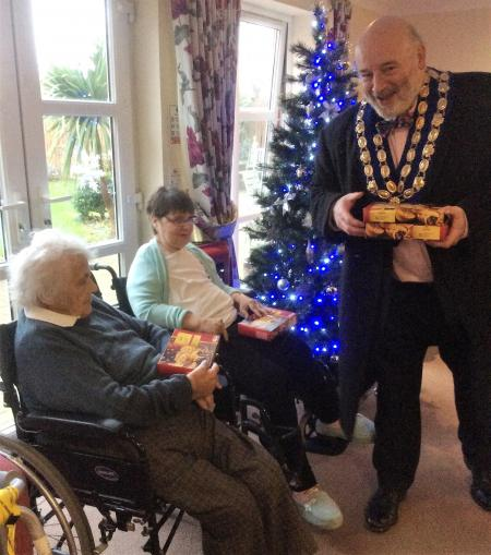 Residents Kathleen Primmer and Pauline Norman receiving some mince pies from the Mayor of Westbury, Ian Cunningham
