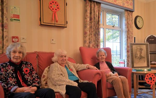 Residents Agnes Smith, Joyce Tatlow, and Joan Wood next to the portrait of her father on Remembrance Sunday