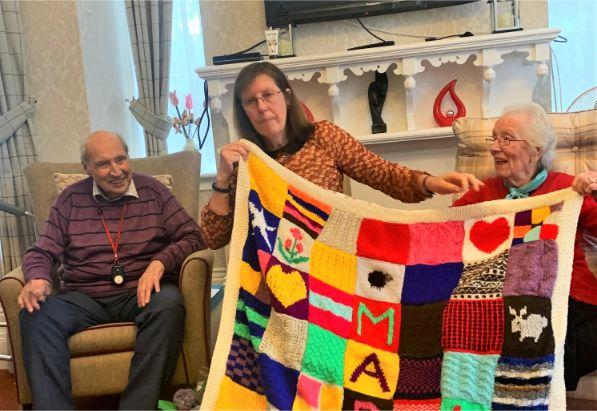 Hamilton House Care Home, Buckingham-Resident John and family members Janet and Edna showing some examples of their work in our knitting lesson