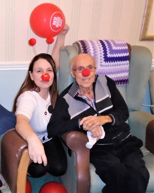 The Grange Care Home, Lancashire. Magic Moments Club Coordinator Kelly and resident Fred having fun on Red Nose Day