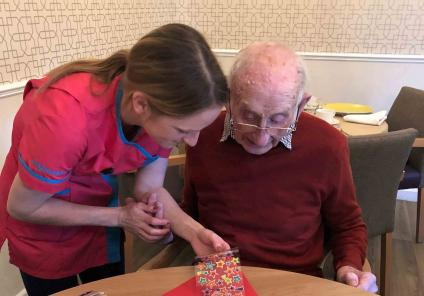 Magic Moments Club Co-ordinator Sarah Gibbs helps resident Ray with his beautiful kite creation!