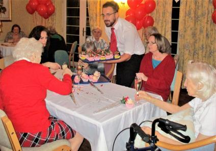 Avery Lodge Care Home, Lincolnshire. Magic Moments Club Coordinator Sam serving cocktails and cupcakes at our Valentine's event