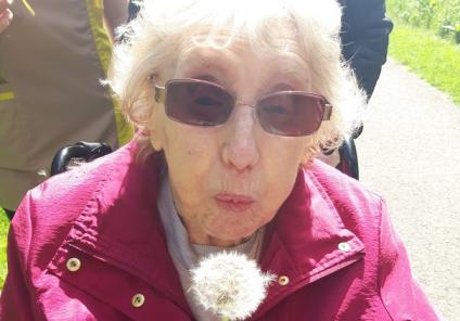 Avery Mews Care Home-Resident Doreen blowing a dandelion clock