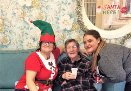 Bamfield Lodge Care Home, Bristol. Carer Bev Johnson, resident Graham Martin and team member Elli Maddocks enjoying Christmas Day together
