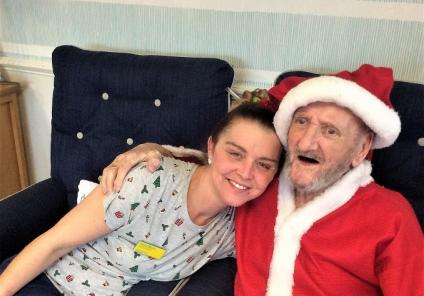 Bamfield Lodge Care Home, Bristol. Carer Donna Morris gets a Christmas cuddle from resident Clifford Baker