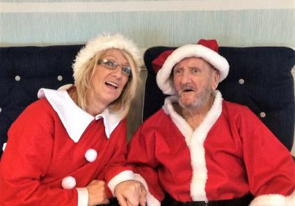 Bamfield Lodge Care Home, Bristol. Magic Moments Club Coordinator Pat Rose and resident Clifford Barker all dressed up for Christmas