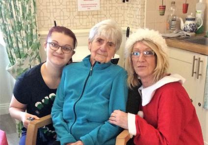 Bamfield Lodge Care Home, Bristol. Resident Joyce Hicks with team members Iryna Dunk and Pat Rose