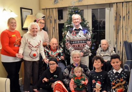 Hall Park Care Home, Nottinghamshire. Resident Graham Clifford (centre) in his wonderful light up Christmas jumper with fellow residents, team members and family and friends on Christmas Day