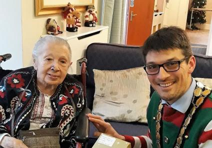 Highfield Care Home, Hertfordshire. The Mayor of Ware, David Oldridge presenting resident Irma with a book, part of a local initiative to spread the joy of the written word